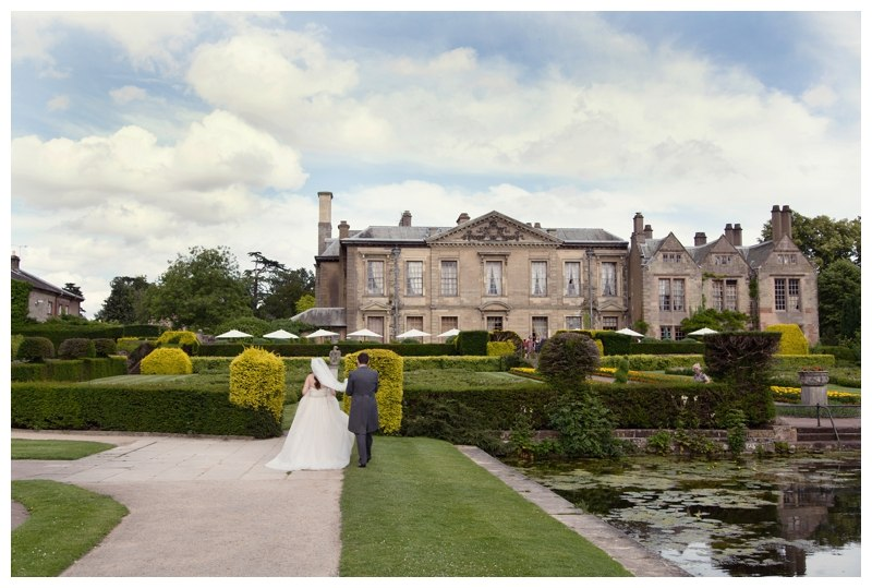 Bride and Groom walking towards Coombe Abbey