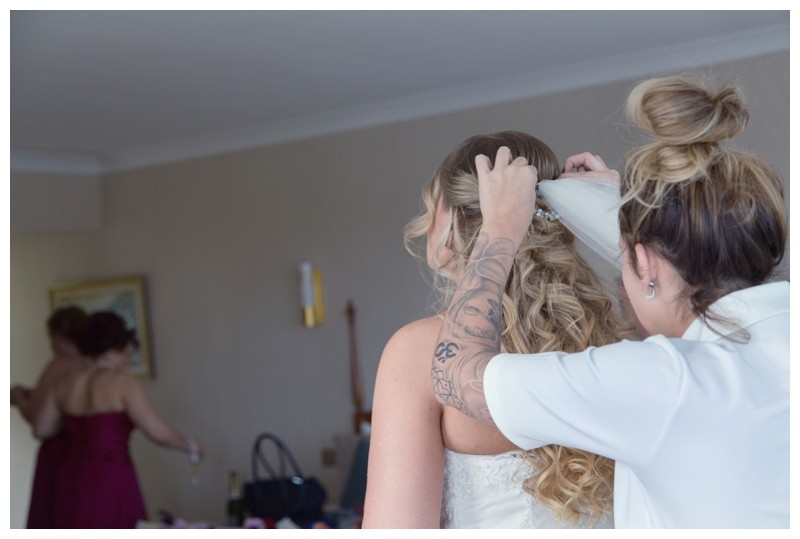Bride having her veil put in