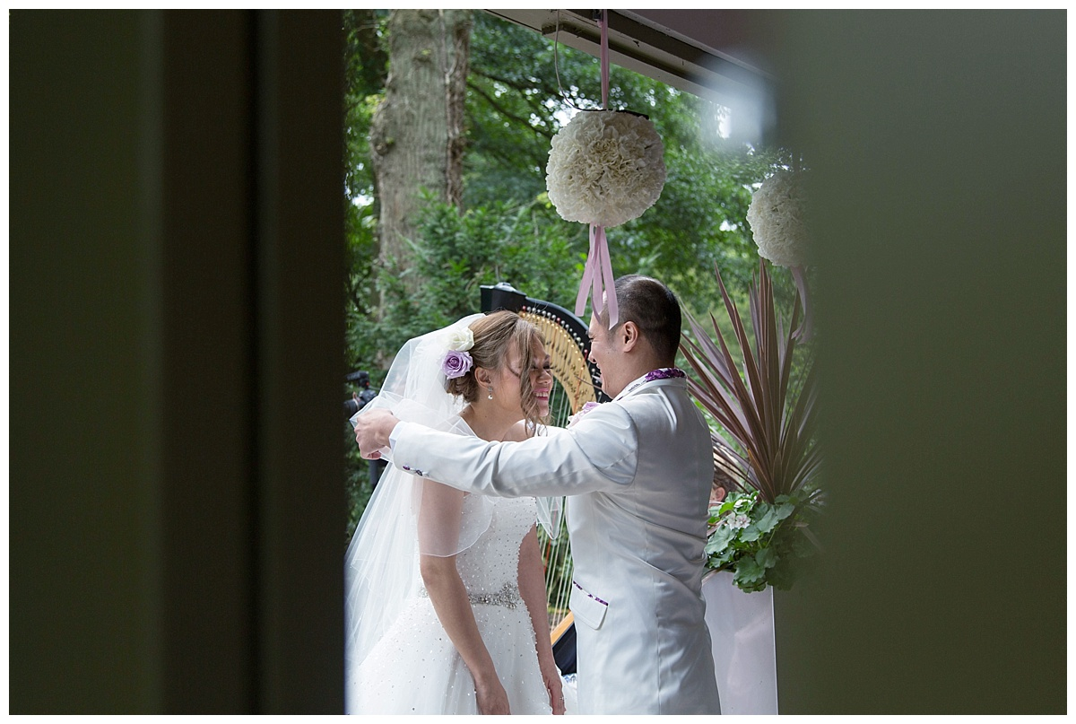 groom taking off brides veil