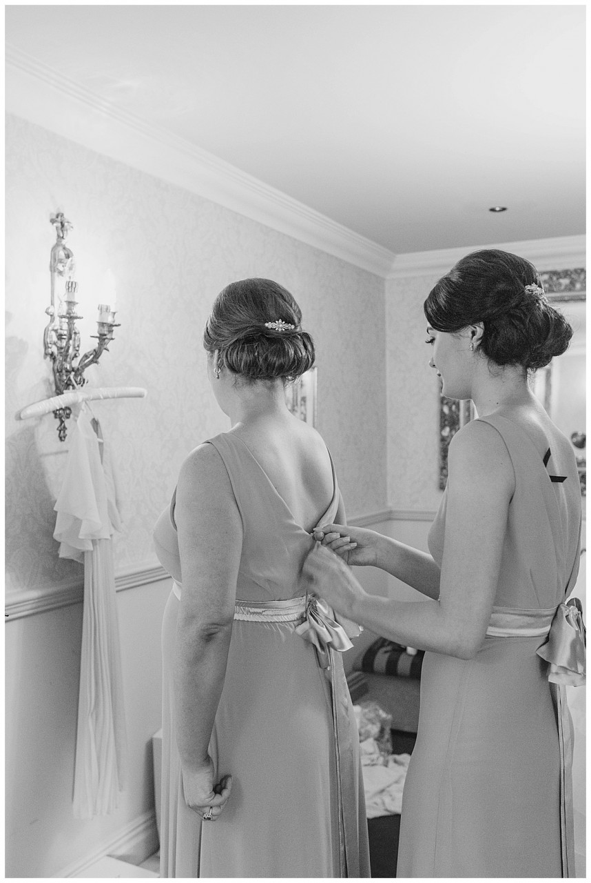 Bridesmaids putting dress on Coombe Abbey